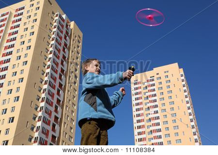 Little Boy In Blue Jacket Plays With Pink Propeller. Two Yellow Multi-storey Building