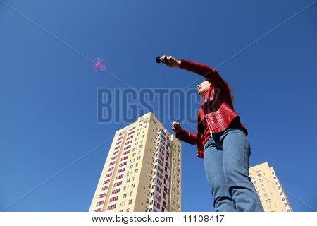 Beautiful Young Woman In Red Jacket And Blue Jeans Playing With Pink Propeller.