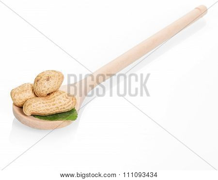 unshelled peanuts in a wooden spoon on white