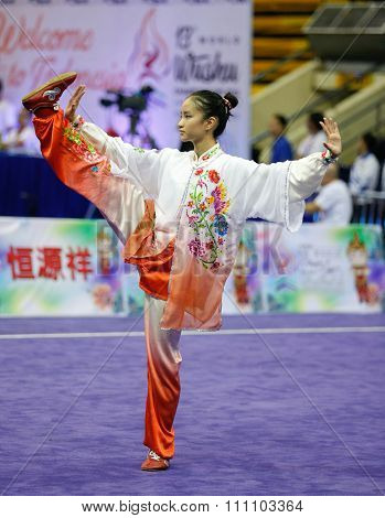 JAKARTA, INDONESIA - NOVEMBER 16, 2015: Vera Tan of Singapore performs her movements in the Women's Compulsory Taijiquan event at the 13th World Wushu Championship 2015 held in Istora Senayan Stadium.