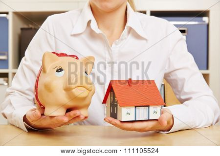Building society savings concept with hands holding house and a piggy bank