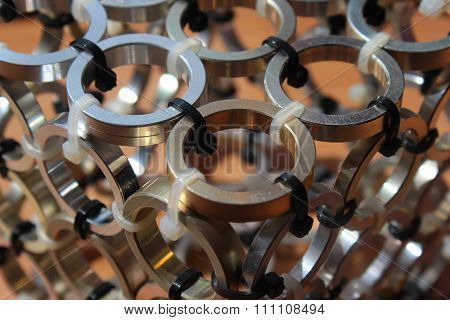 Abstract Background Of Small Metal Rings Concatenated With Plast