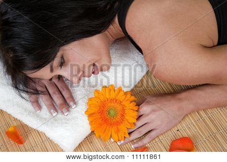 Woman lying on bamboo mat at spa, surrounded by flower petals