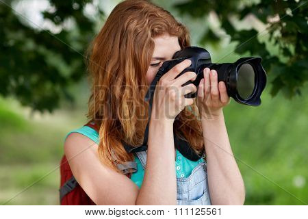 travel, tourism, hike, hobby and people concept - young woman with backpack and camera photographing outdoors