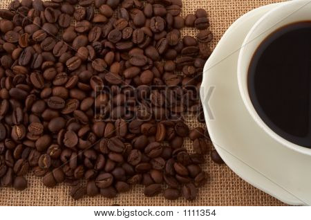White Cup Of Black Coffee And Coffee Beans