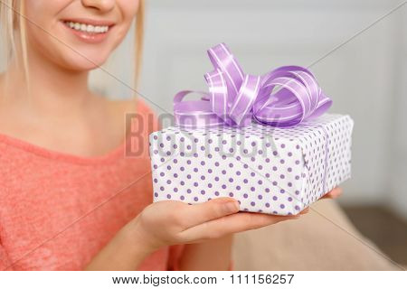 Young smiling woman holding a wrapped present.