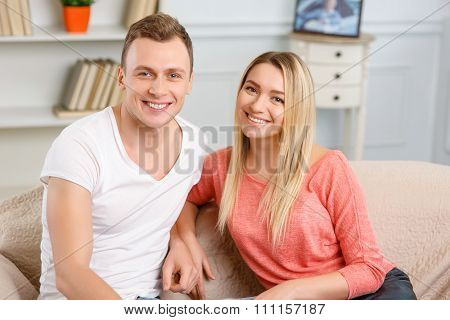 Young smiling couple sitting on the sofa.