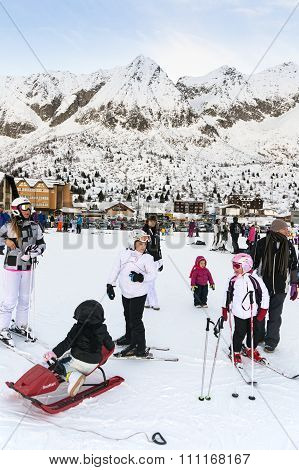 Families On Holiday On The Slopes Of The Italian Alps.