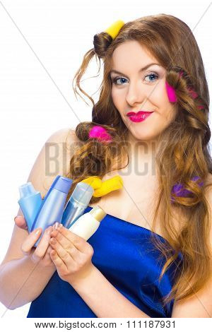 Beautiful Woman With Long Hair In Curlers Holding Products In Her Hands