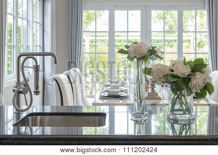 Glass Vase Of Flower On Black Granite Counter