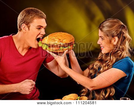 Woman feeds man fast food. Concept.