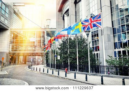 Waving Flags In Front Of European Parliament Building. Brussels, Belgium