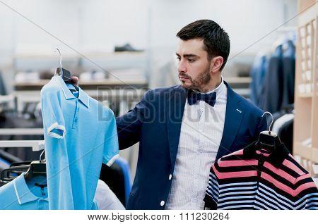 Attractive Young  Man Chooses Tee - Shirt At A Shop.