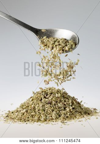 Dried Oregano Falling From Tablespoon