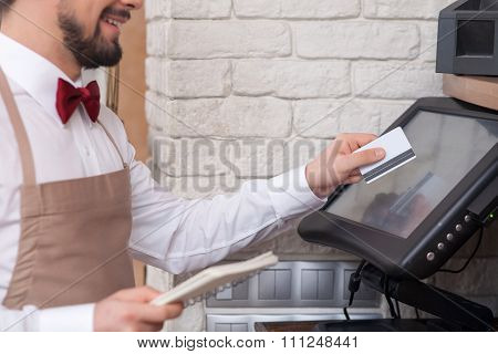 Cheerful young waiter is working with checking machine