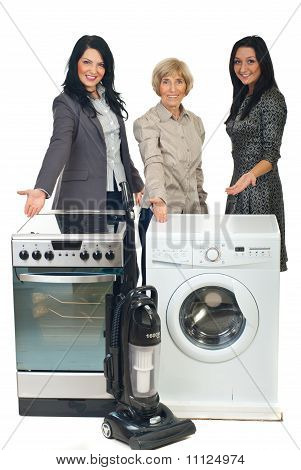 Three Sales Women Showing To Household Appliances