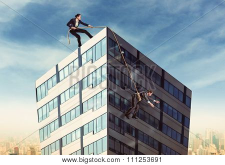 Businesswoman pulling businesswoman on the roof with a rope