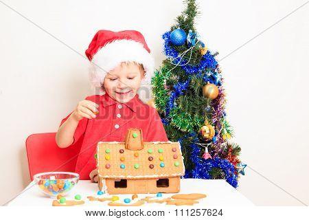 little boy in Santa's hat building gingerbread house
