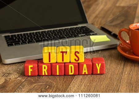 Its Friday written on a wooden cube in a office desk
