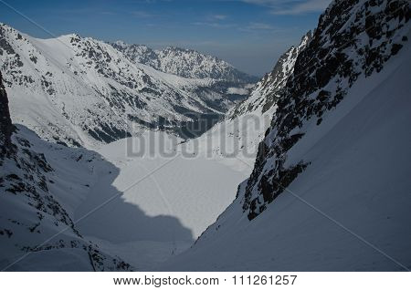 A lake is in a mountain winter valley