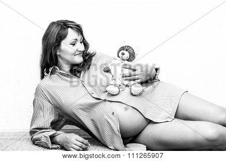 Happy Pregnant Woman Lying On The Floor.