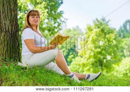 Beautiful Woman 50 Years With A Book Near A Tree On The Lawn In The Park