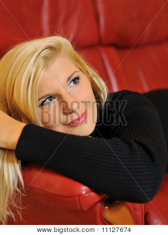 Portrait Of A Casual Woman Relaxing And Smiling At Home At Red Sofa