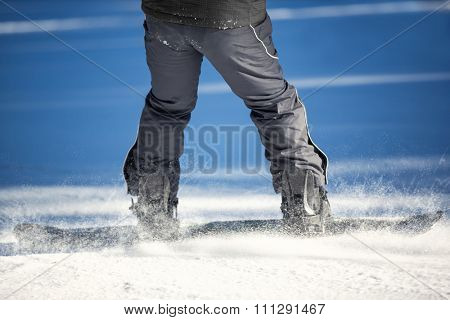 Legs of snowboarder in action