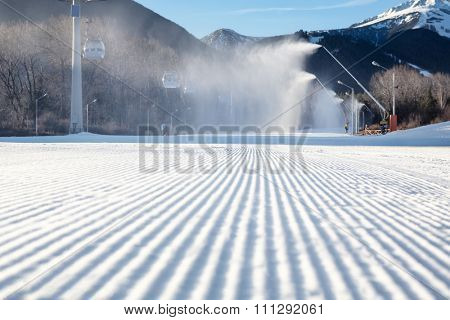 perfectly groomed empty ski run with snow cannon which is making powder snow