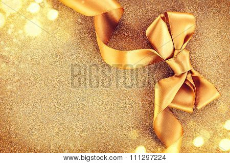 Christmas Golden Satin Ribbon Bow on a Blinking Holiday Background. Greeting Card with copy space for your text. Beautiful Gold Christmas Gift Border art design