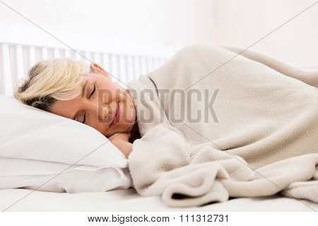 pretty senior woman sleeping on bed