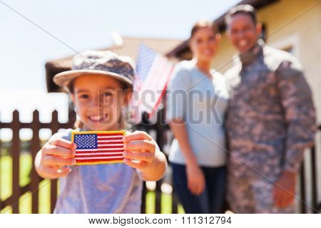 little girl holding american flag badge in front of parents