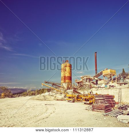 Gear and machines at a gravel pit shot on a clear sunny day shot with tilt and shift lens