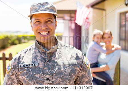 cheerful american military soldier standing in front of family