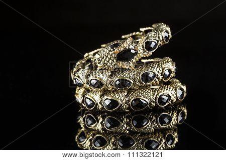 golden bracelet form of snake isolated black background