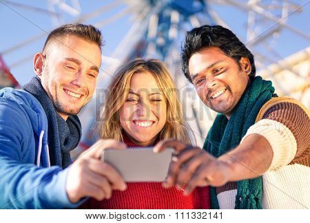 Group of multiracial best friends taking a selfie in front of ferris wheel - Happy people having fun
