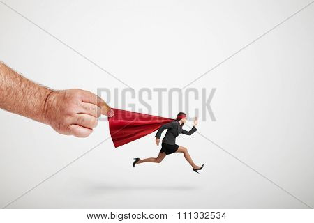 big mans hand holding the red cloak of running superwoman over light grey background