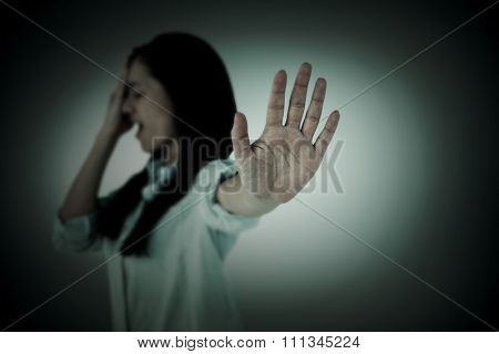 Irritated woman showing her hand against grey vignette