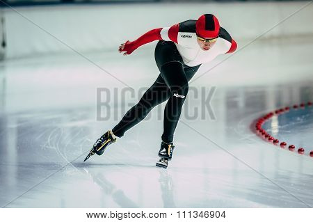 closeup young woman athlete speedskater goes around turn of rink