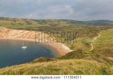 Worbarrow Bay east of Lulworth Cove and near Tyneham on the Dorset coast England uk with a yacht