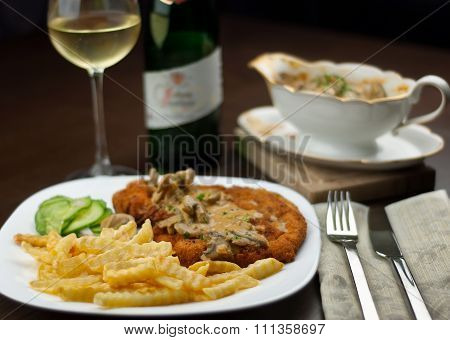 Schnitzel, French Fries, Cucumber Salat And White Wine With Jaeger Sauce