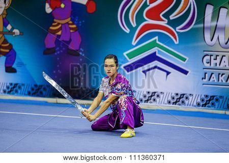JAKARTA, INDONESIA - NOVEMBER 17, 2015: Thuy Linh Nguyen of Vietnam performs the movements in the women's Nandao event at the 13th World Wushu Championship 2015 held in the Istora Senayan Stadium.