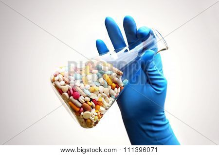 A lot of pills in the Erlenmeyer flask in the hand