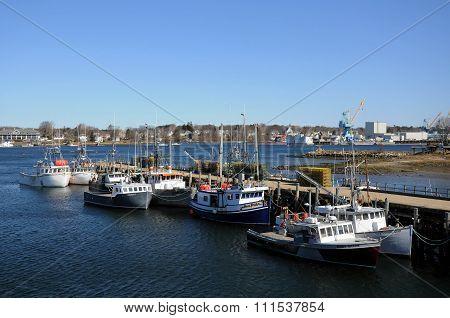 Fishing boats resting along side a dock