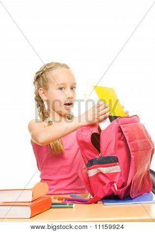 Little beautiful schoolgirl is packing her rucksack
