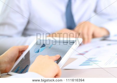 Business Colleagues Working And Analyzing Financial Graphs On A Digital Tablet