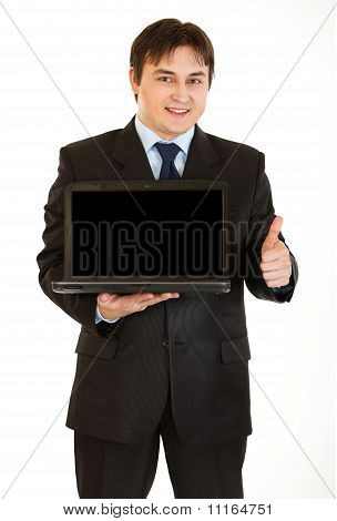 Smiling young businessman holding laptop with blank screen and showing thumbs up gesture isolated on