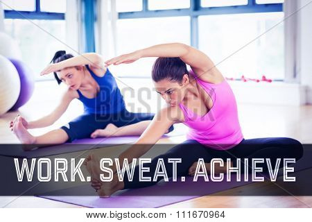 Fit women doing stretching pilate exercises against motivational new years message