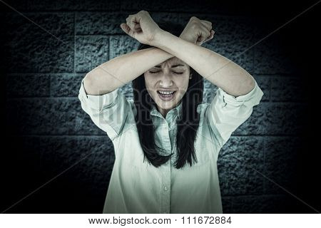 Troubled woman crying against dark grey room