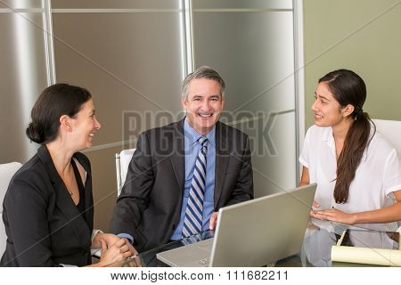 Mature business man with team members in an office